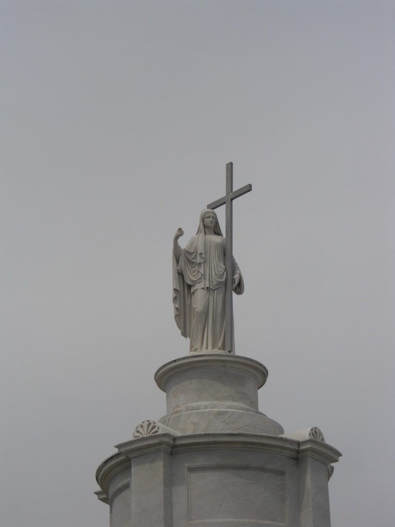 The Tallest Statue Overlooking The Cemetery. It Sits On A Tomb.