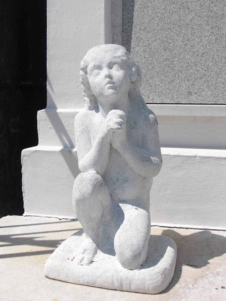 An Angel Statue Standing Guard In Front Of Tomb