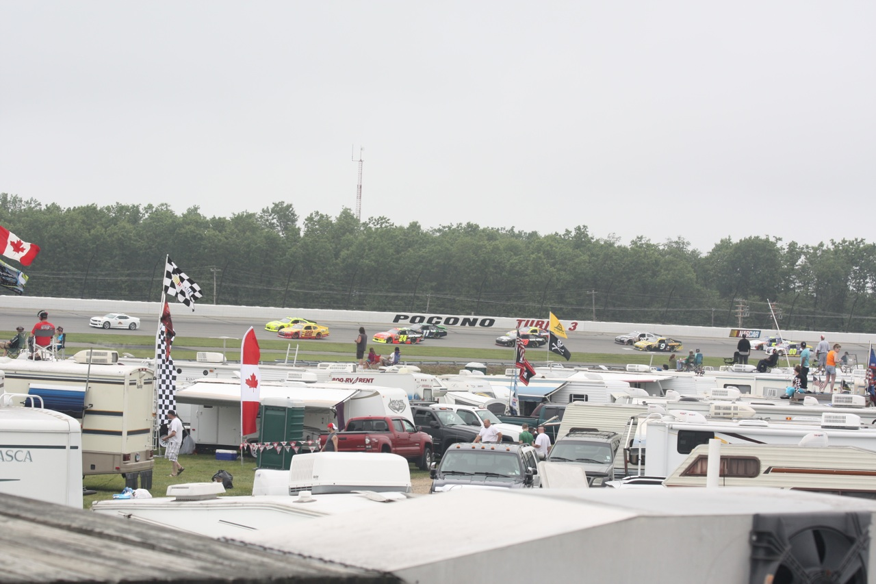 The Race Cars Going Around The Track In The Background