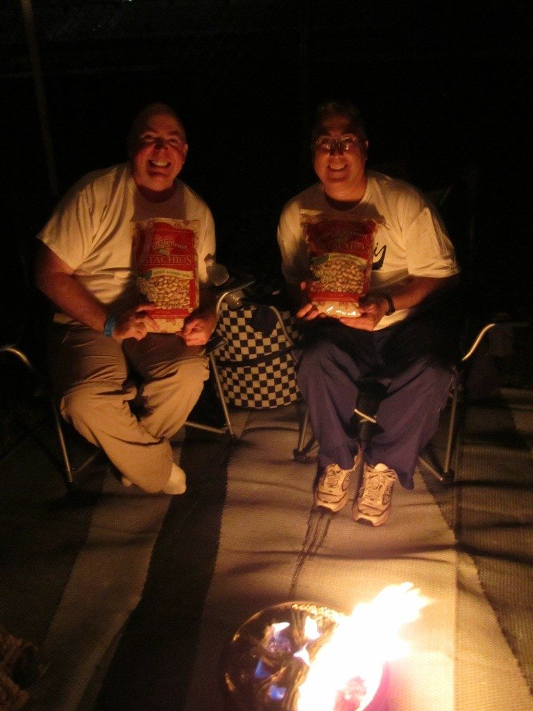 David And Joe Around The Campfire With Their Bags Of Pistachios.