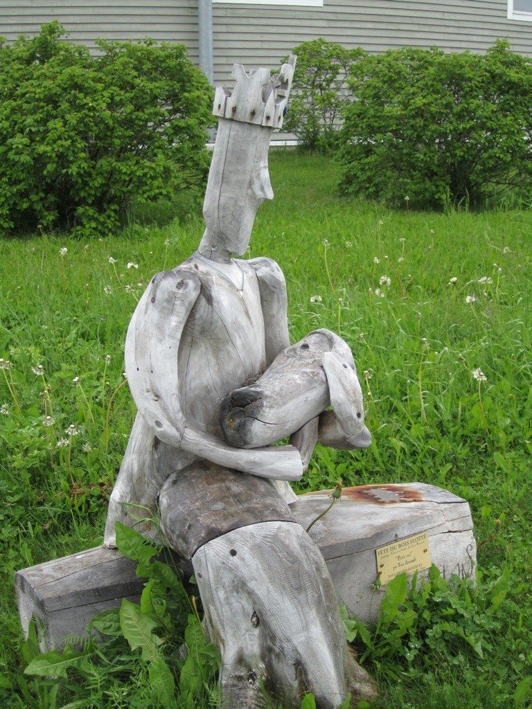 King Holding Baby Driftwood Sculpture In Sainte Anne des Monts.
