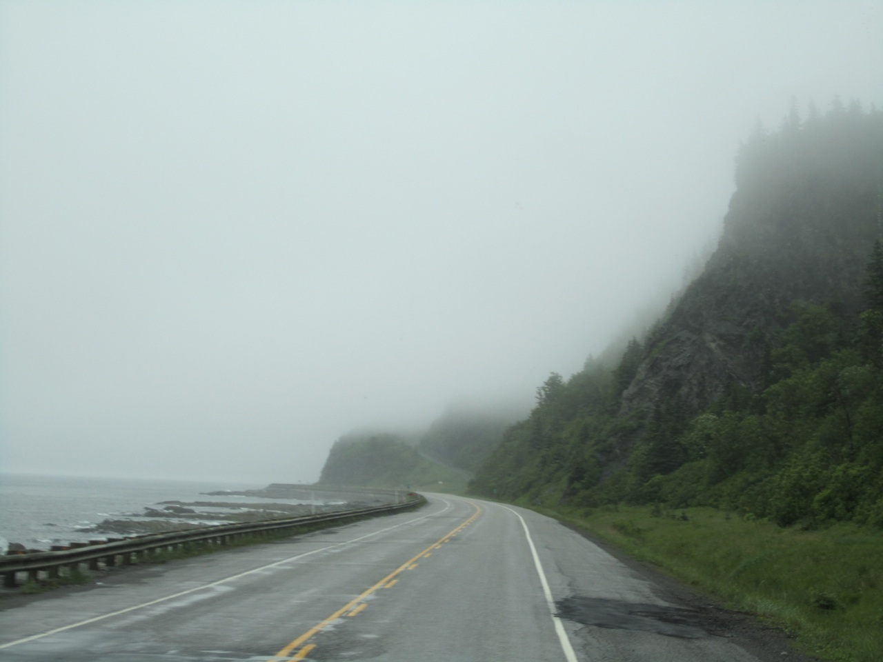 The Road Leading Into Fog.  Water On One Side And Mountains On The Other.
