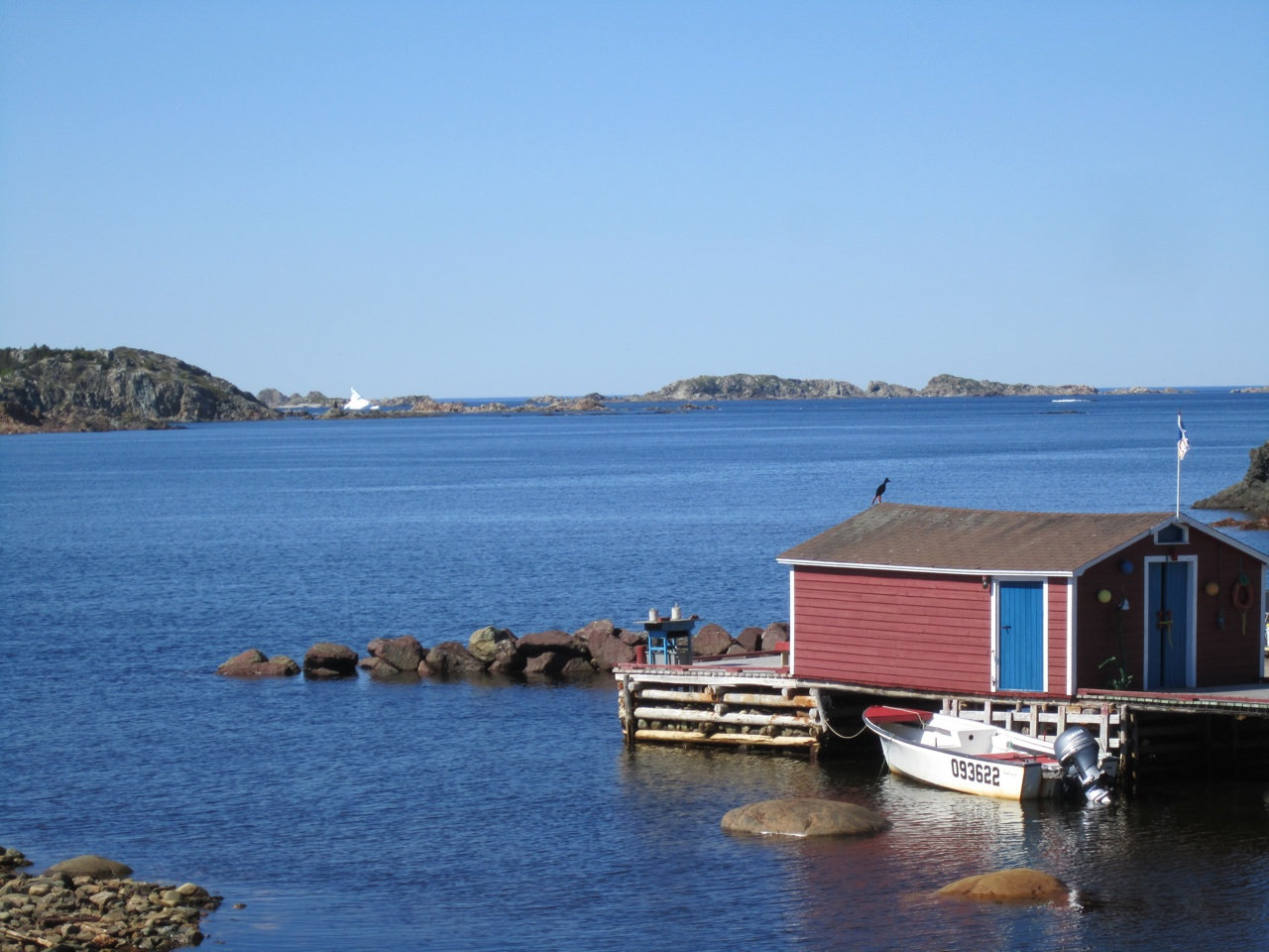 Docks And Fishing Shacks Over The Waters In Twillingate.  Iceberg In The Far Background.