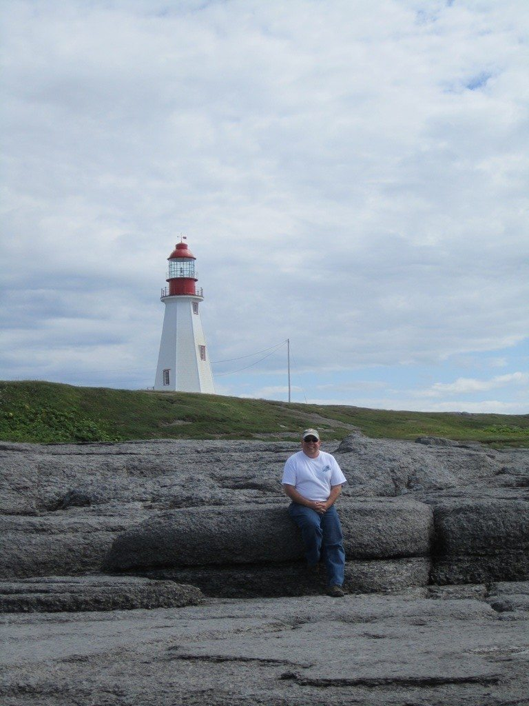 David On The Rocky Shore With The Lighthouse In The Background At Point Riche In Port au Choix.
