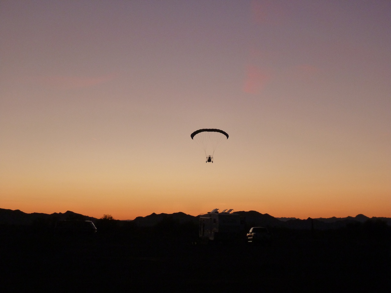 People Flying In Their Powered Parachute Into The Sunset