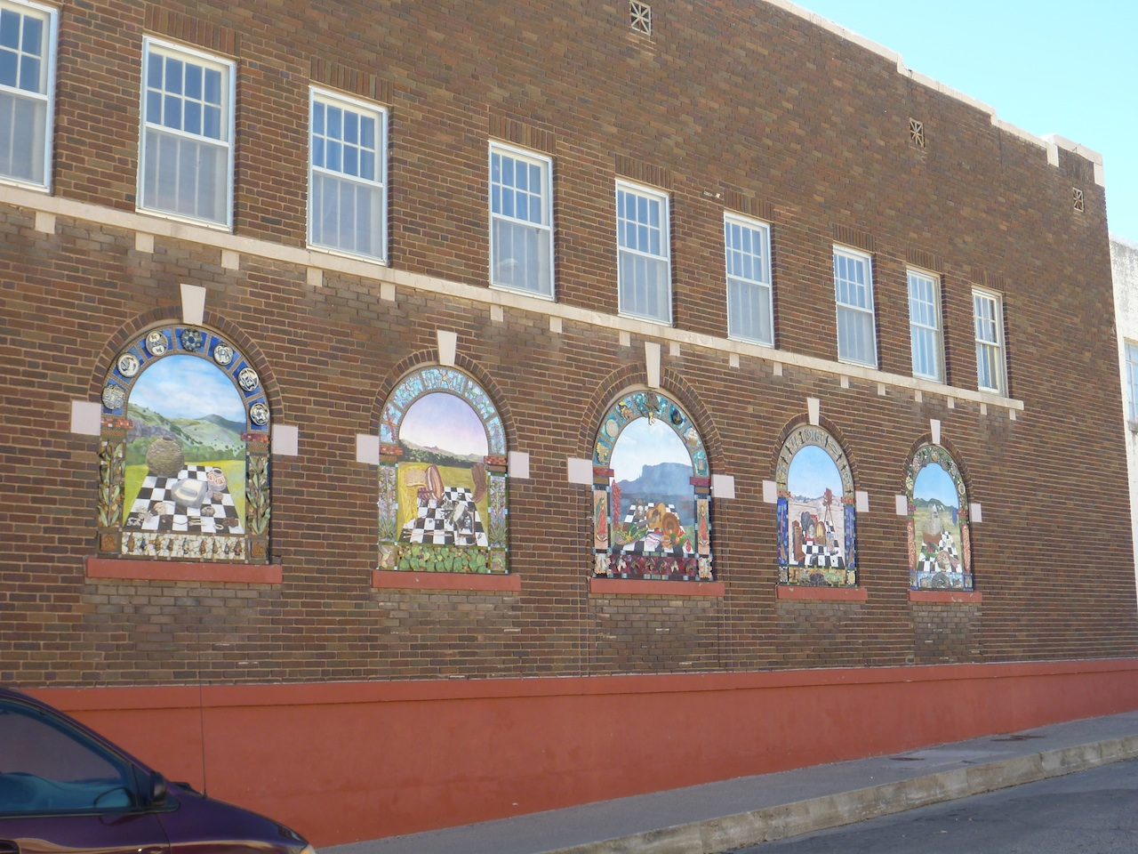 Mural Painted On Window Inserts.  There Are Plates And Tiles Protruding From The Wall Art Also