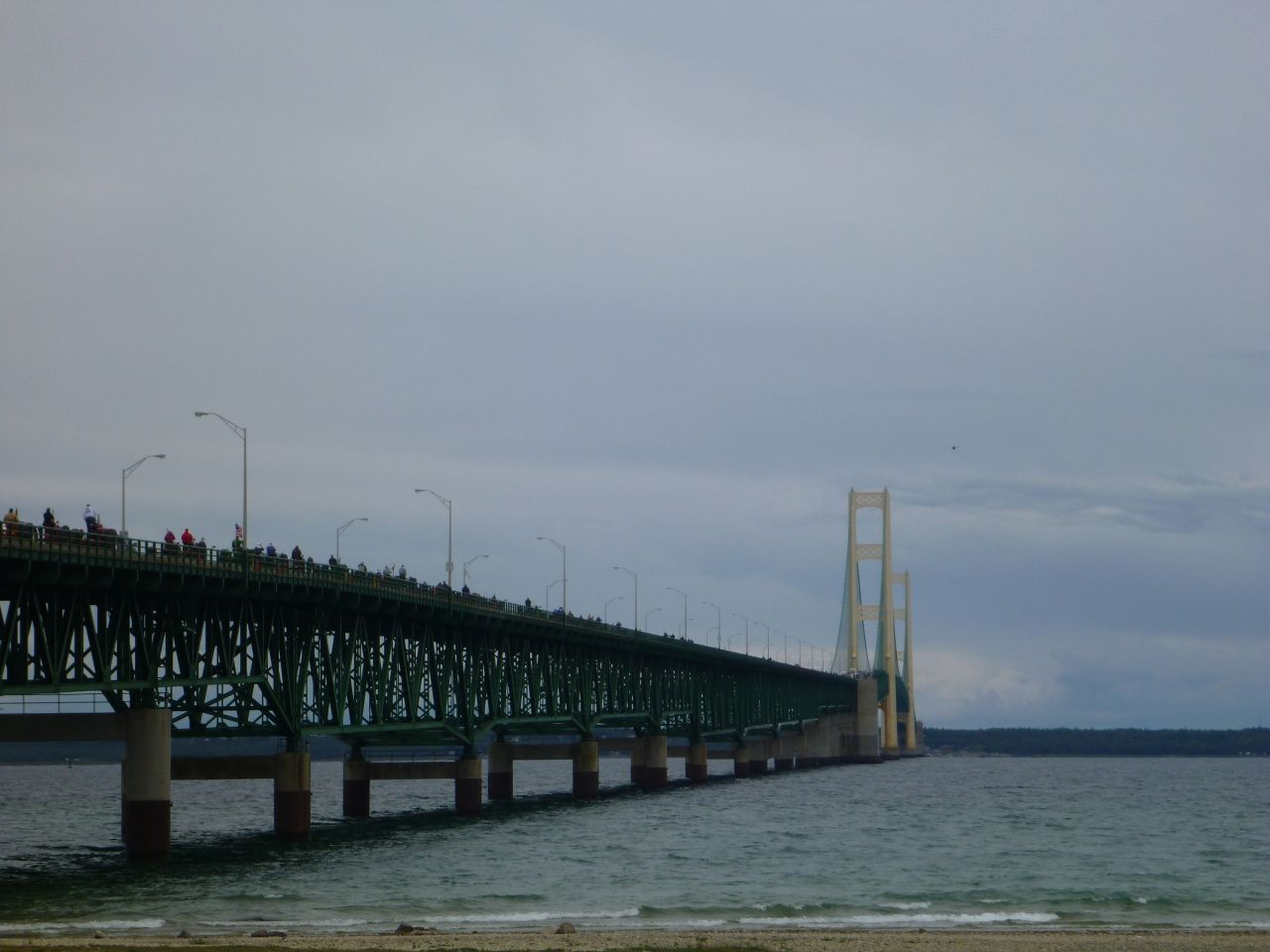 Tractors Crossing The Mackinac Bridge.  The Quadcopter Is In The Background In The Top Right Corner.