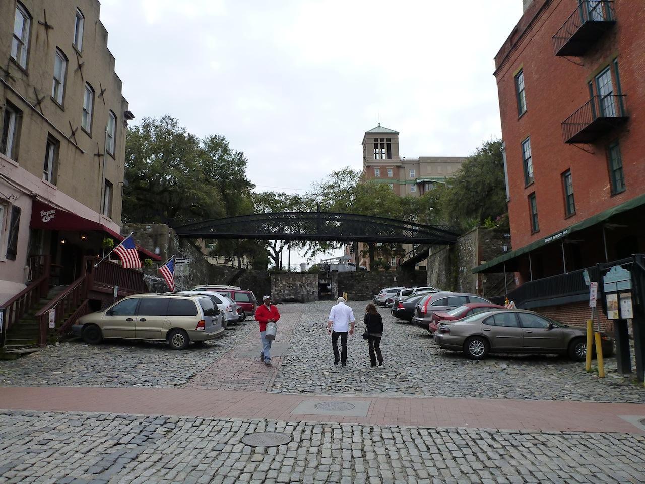 A Pedestrian Bridge Over The Cobblestone Street